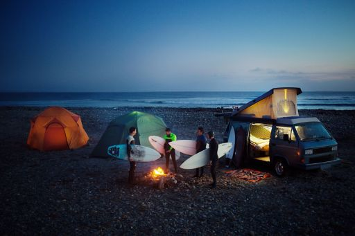 Friends with surfboard camping at beach against sky