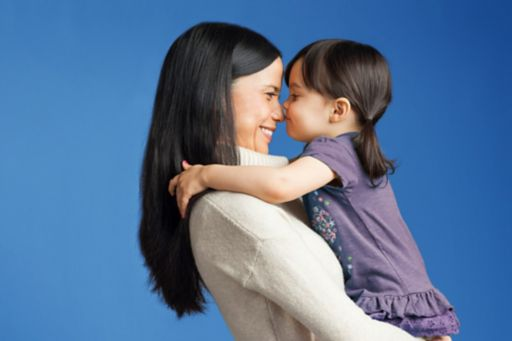 A mother holds her young daughter against a bright blue background