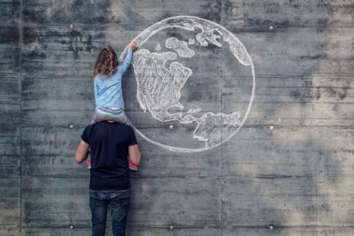 Girl drawing earth on wall sitting on fathers shoulders