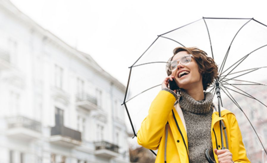 Girl holding an umbrella and wearing a yellow jacket is laughing while talking on the phone