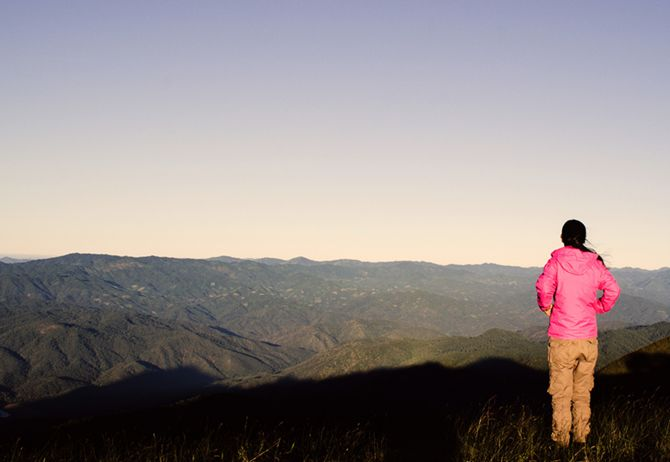 Girl in pink jacket looking at the mountains