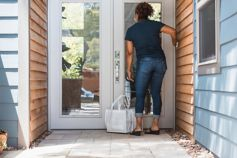 Girl waiting at the door with shopping bags