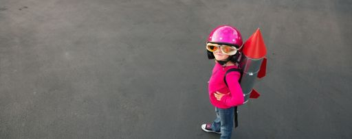 Girl wearing pink helmet dummy rocket bag-pack standing on road