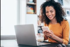 Girl weraing yellow top in front of laptop looking at mobile