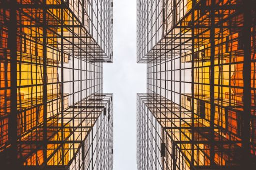 Glass building on both sides with sky in center