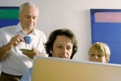 Grandson and grandfather looking at laptop