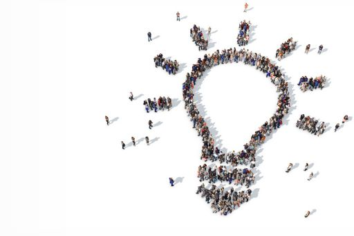 group of people forming a light bulb icon