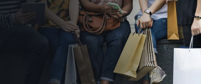 Group of women sitting together while having casual conversation holding shopping bags
