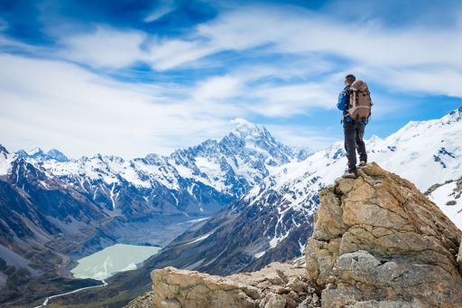 Guy standing on top of snowy mountain