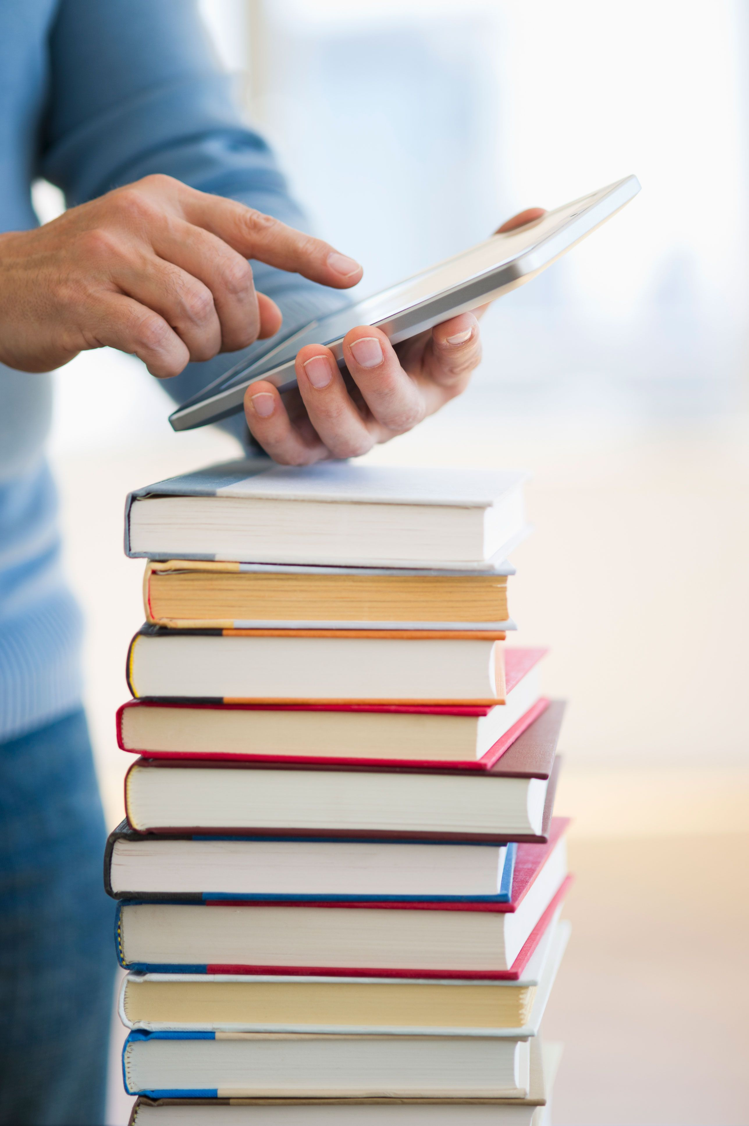 man using a smartphone with a stack of books