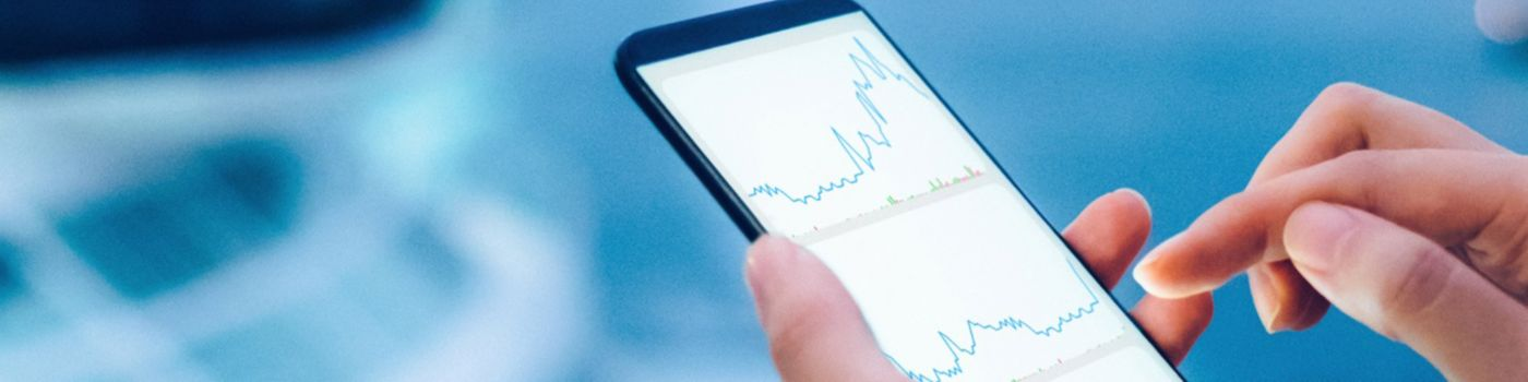 Hand holding mobile showing graph