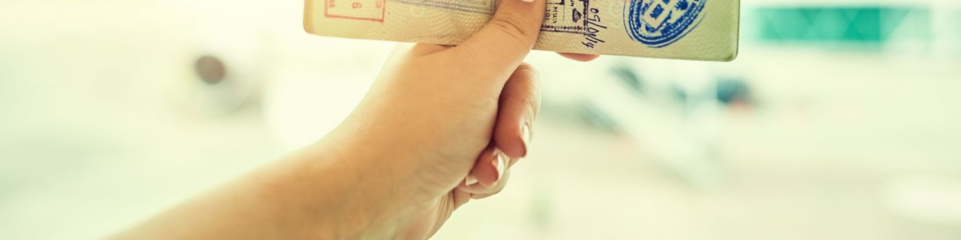 Hand holding passport with lots of visa stamps
