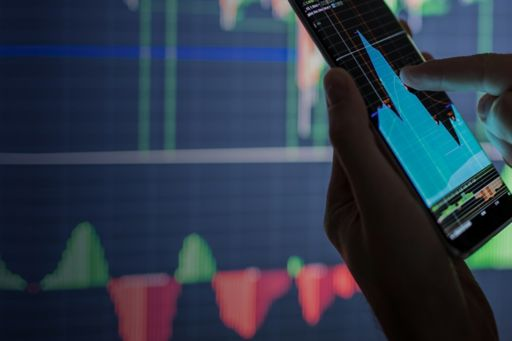 Hand holding phone displaying graph