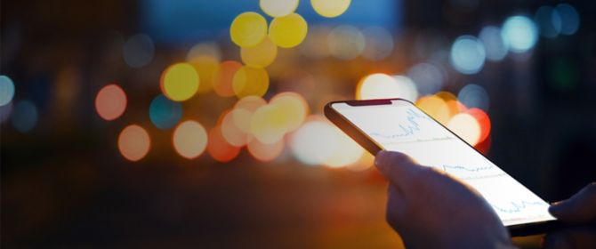 Hand holding phone with graph against background of light