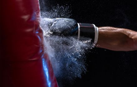 Hand in boxing glove punching sand bag