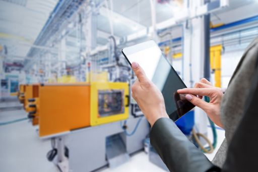 Hands holding a digital tablet in a manufacturing plant