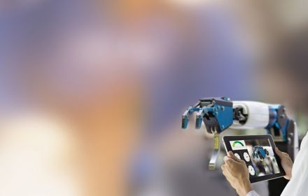 Hands holding tablet laptop against robot arm with blur background