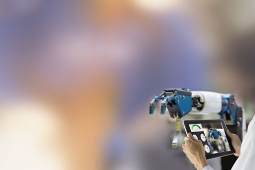 hands-holding-tablet-laptop-against-robot-arm-with-blur-background