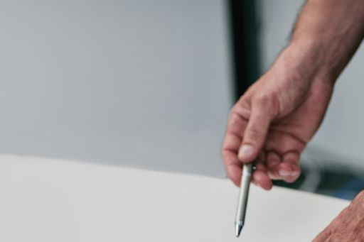 Hands pointing on graph paper over white table
