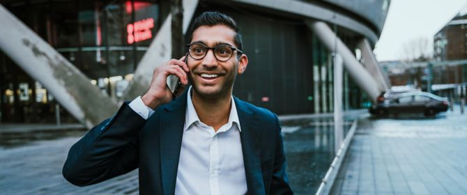 Happy businessman talking on mobile phone while working on laptop outside office