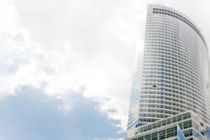 Hemispherical skyscraper with white clouds in sky