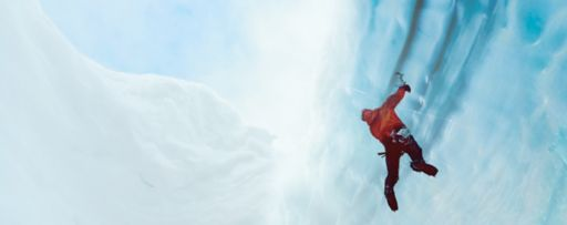 Man climbing wall of ice cave