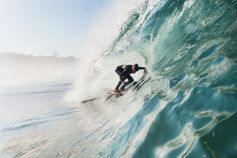 Surfer surfing inside barrel of wave