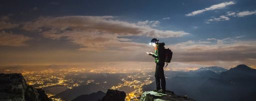 Hiker checks his device on top on the mount