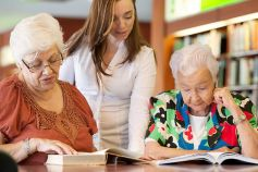 Teacher helping elderly people in a library