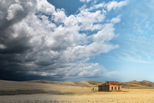 House in a dry field with storm clouds approaching