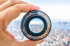 Hand holding lens on background of a city.