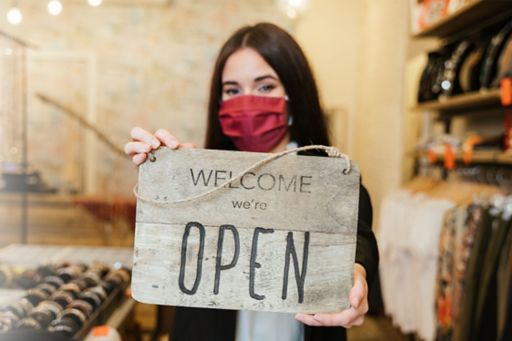 Retail worker wearing mask and holding Open sign