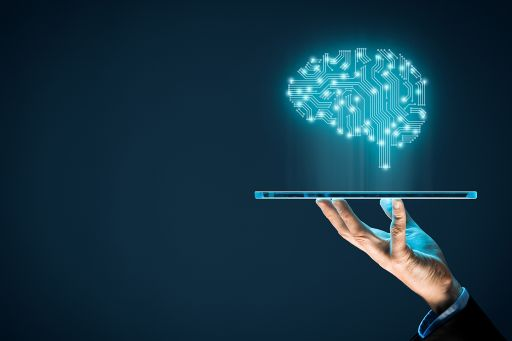Hand holding a tablet which projects a neon brain image