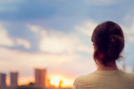 Woman looking at sunset behind skyscrapers