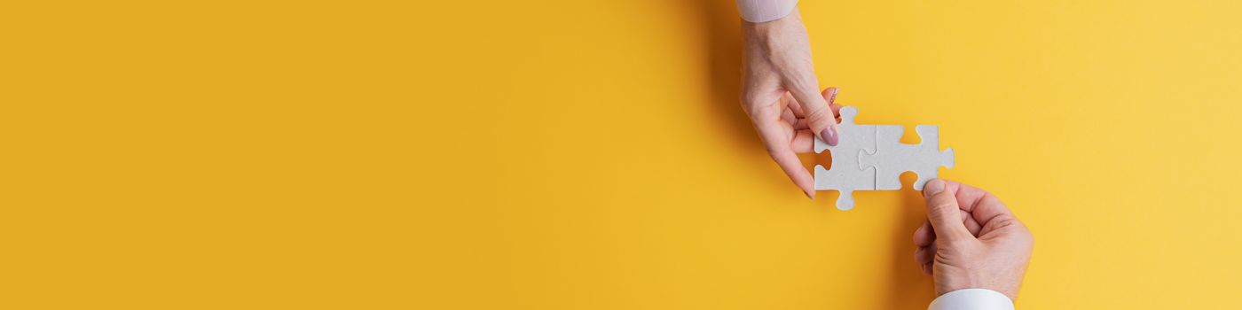 Two hands doing a jigsaw on a yellow background