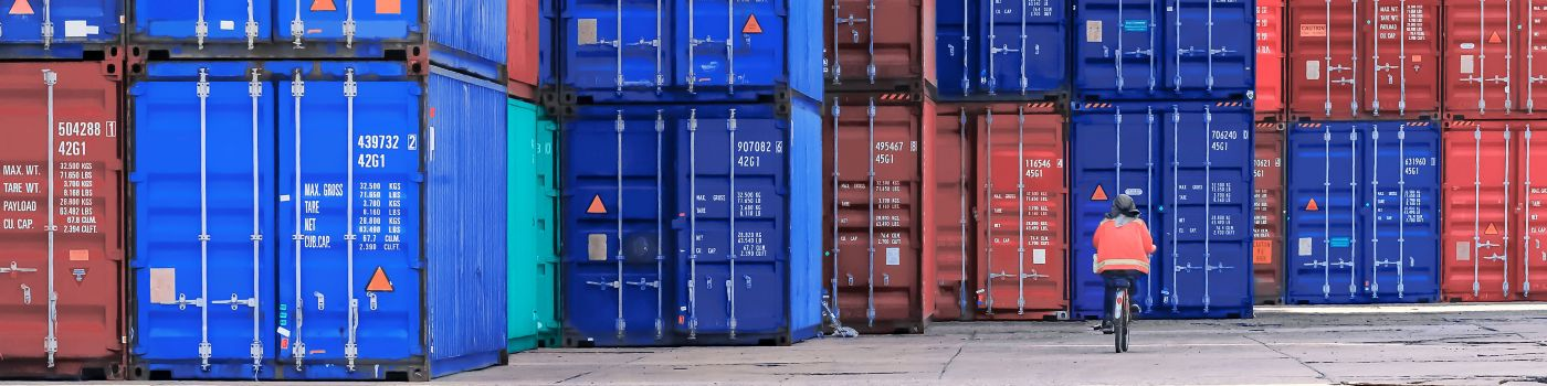 Worker cycling past shipping containers