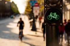Green bike traffic light with cyclist in background