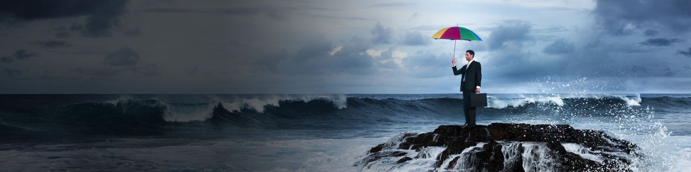Business man stands on rock in raging sea