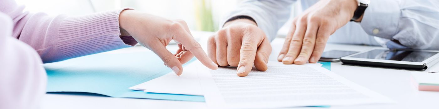 Hands pointing at papers in meeting