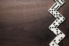 Building a tax technology strategy - zig zag column of dominoes on wood table background