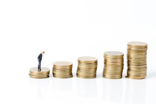 Businessman miniature toy and stacks of coins