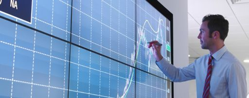 Man drawing on graph on large screen