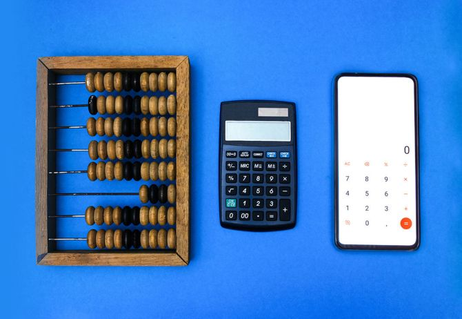 Abacus, calculator and smartphone on blue background