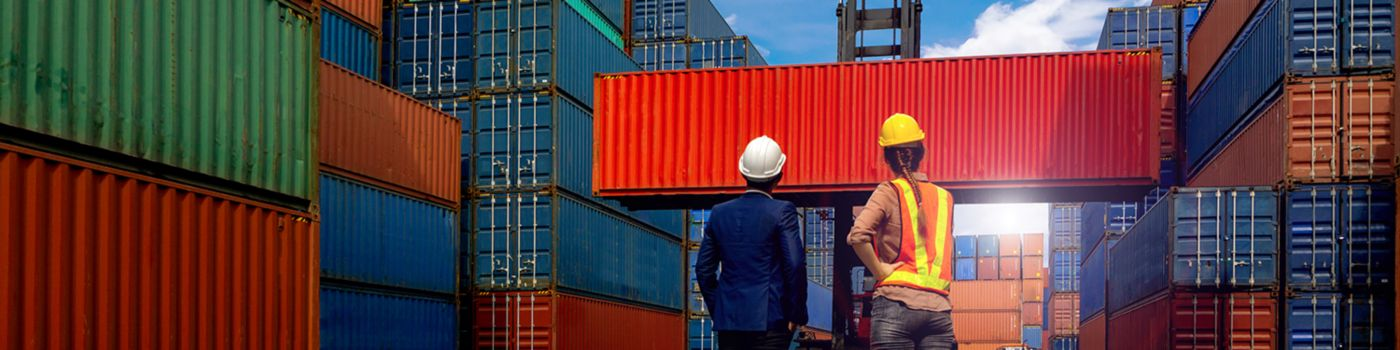 Two men talking surrounded by shipping containers