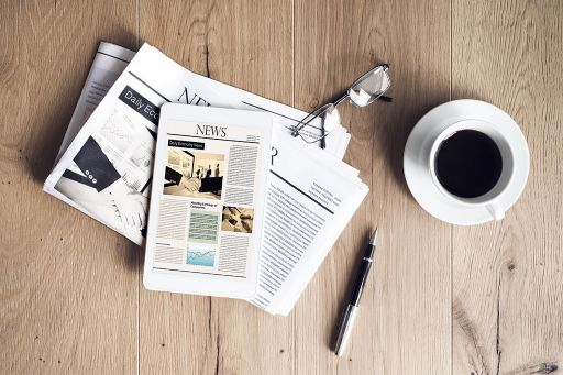 Newspapers and tablet on table with coffee