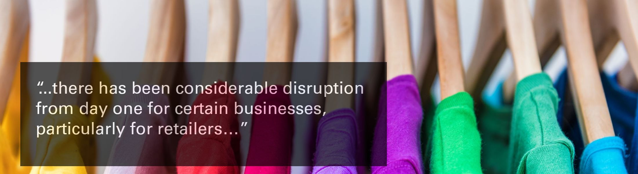 "Image of hangers holding a variety of coloured tshirts, with text overlaid, ""there has been considerable disruption from day one for certain businesses, particularly for retailers"""