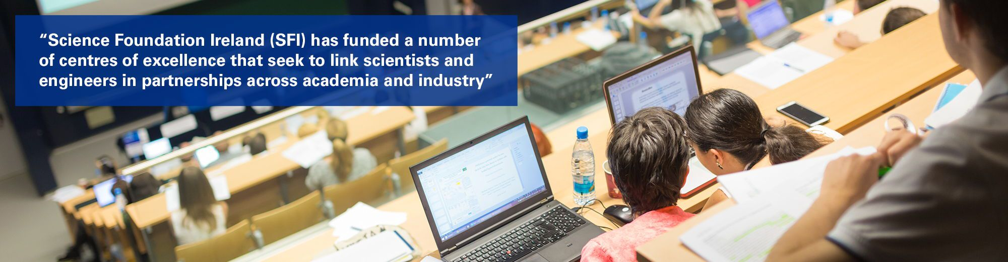 """Two people in lecture hall with text overlaid """"Science Foundation Ireland (SFI) has funded a number of centres of excellence that seek to link scientists and engineers in partnerships across academia and industry"""""""