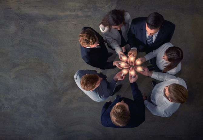 Team in a circle holding lightbulbs in the palm of their hands