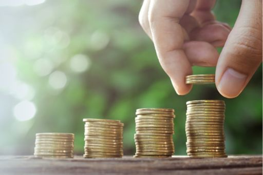 Hand placing coins in increasing piles