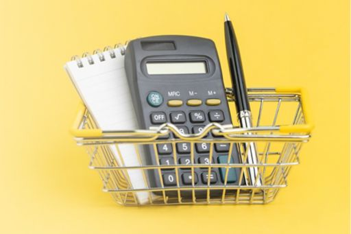 Calculator, notepad and pen in mini shopping trolley